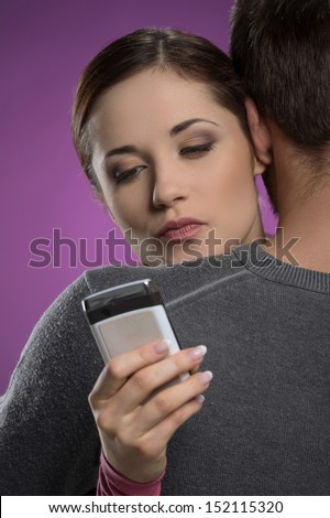 Infidelity. Attractive young woman typing a message on her mobile phone while hugging with her boyfriend - stock photo