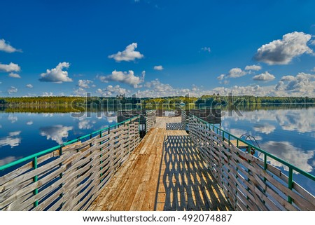 Infinity pier at picturesque summer lake with clouds reflecting in still water