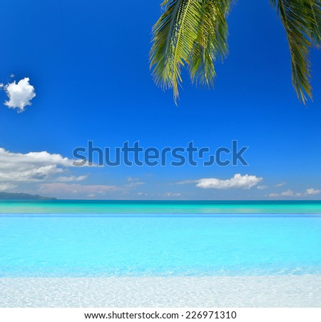 Infinity pool at tropical beach  - stock photo