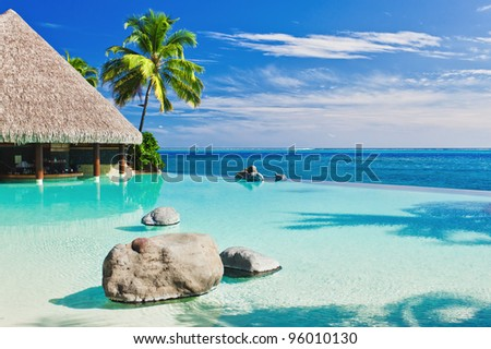 Infinity pool with palm tree overlooking tropical ocean - stock photo