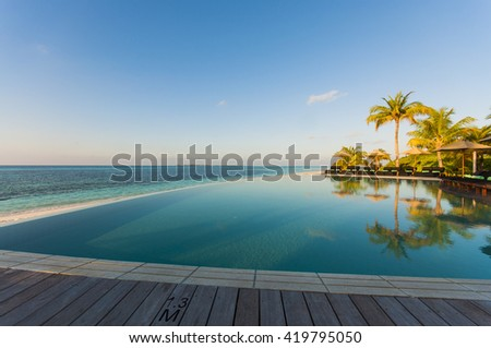 infinity pool with sea views and palm trees - stock photo