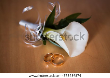 infinity sign of the rings, wedding rings on a white background,wedding bands, white boutonniere of calla, wedding jewelry, wedding preparation, wedding rings and flowers  - stock photo