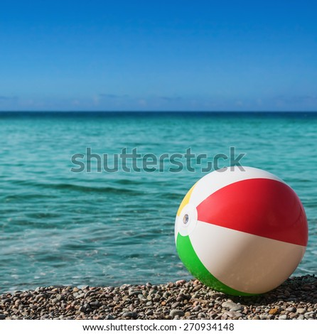 inflatable ball on the beach against the backdrop of the ocean. Focus on the ball - stock photo