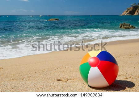 Inflatable beach ball in the sand near the water line at the Spanish beach - stock photo
