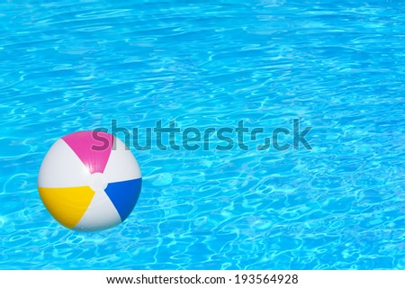 Inflatable colorful ball floating in swimming pool - stock photo