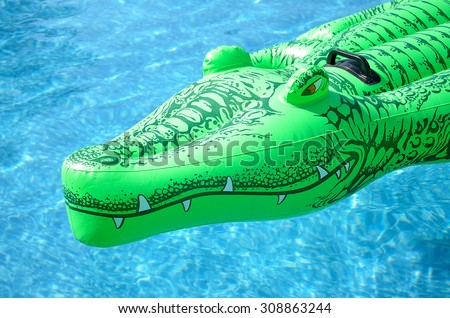 Inflatable Deck Chair In The Shape Of A Crocodile In The Pool