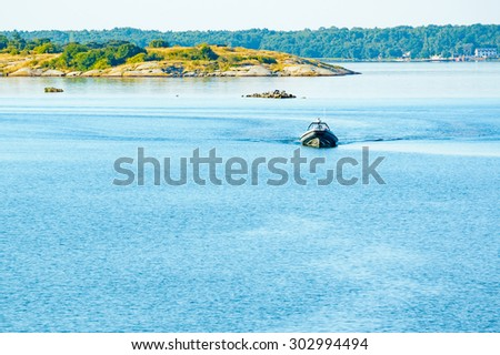 Inflatable rubber boat coming towards you at slow speed. Open sea in front of vessel and islands in background. Calm sea with small surge from the boat. Copyspace. - stock photo