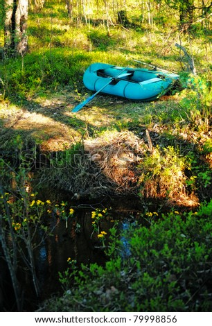 inflatable rubber boat on river shore at forest - stock photo