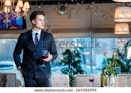 informal business meeting. Young man businessman in formal wear standing in a restaurant while holding a glass of wine and looking forward - stock photo