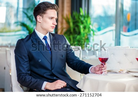 Informal meeting at the restaurant. Confident businessman in formal wear sitting at a table in a restaurant while holding a glass of wine and looking away - stock photo