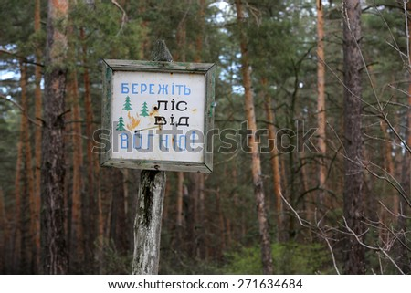 Information board in forest with message in Ukrainian: keep forest from fire
