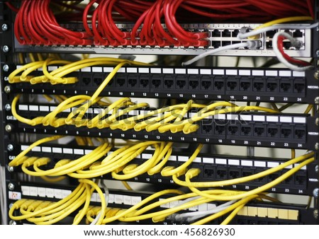 Information Technology Computer Network, Telecommunication Ethernet Cables Connected to Internet Switch. Security protection. network cables installed in rack. Server. UTP Cat5e Cable with patch panel - stock photo