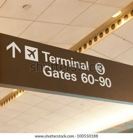 Informational sign showing gate numbers at international airport. - stock photo