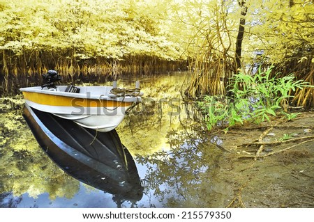 Infrared edited image of reflection floating boat and trees at the river bank - stock photo