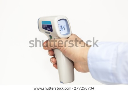 Infrared medical thermometer in hand - stock photo