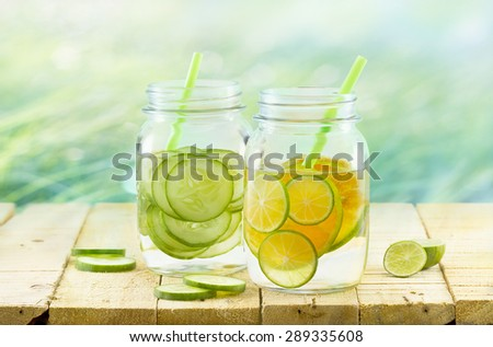 Infused detox and diet water, lemon and cucumber on wooden nature background, vintage and pastel color tone