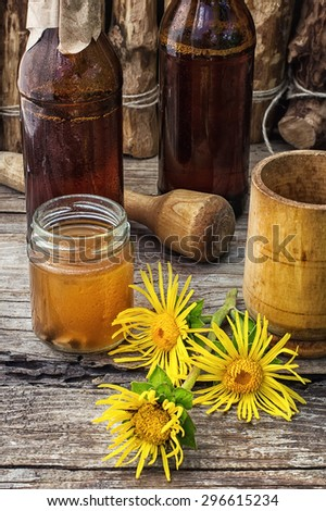infusion of inflorescences and roots of the medicinal plant Inula on the wooden table next mortar and pestle.Photo tinted.Selective focus - stock photo