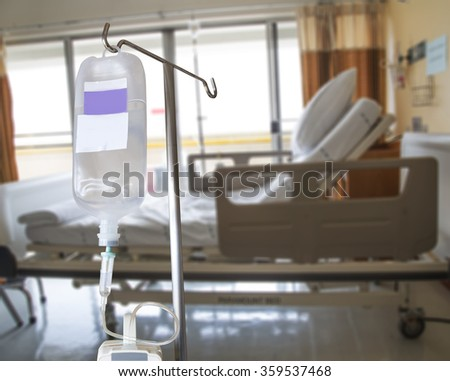 Infusion pump and IV hanging on pole in patient room - stock photo