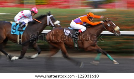 "INGLEWOOD, CA - DEC 15: Jockey Alex Bisono and ""Tiz Dynamic"" (lead horse) charge ahead of rivals to win a claiming race at Hollywood Park on Dec 15, 2012 in Inglewood, CA. - stock photo"