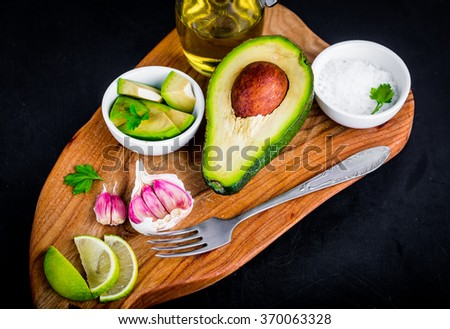 Ingradients for homemade guacamole: avocado, lime, salt and garlic. - stock photo