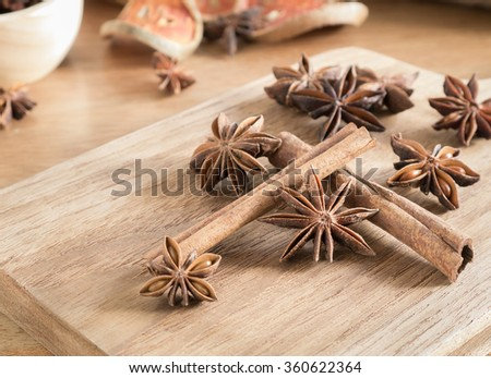 ingredient flavor aromatic- Star anise and cinnamon sticks on wooden chopping block - stock photo