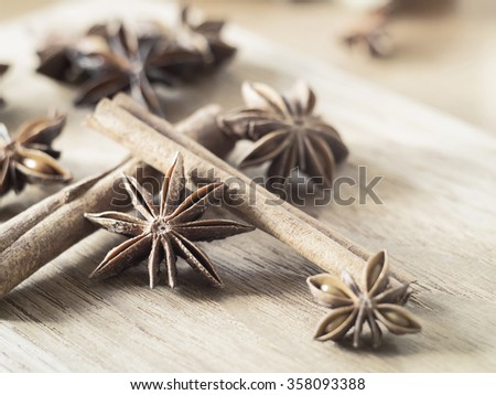 ingredient flavor aromatic - Star anise and cinnamon sticks on wooden chopping block ( Vintage tone color ) - stock photo