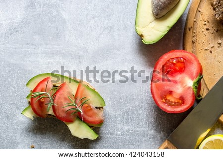 Ingredients and freshly prepared sandwich with avocado, rye bread, tomatoes, concept of healthy food, nutrition and omega fatty acids - stock photo