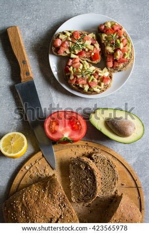 Ingredients and freshly prepared sandwiches with avocado, rye bread, tomatoes, concept of healthy food, nutrition and omega fatty acids - stock photo