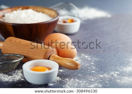 Ingredients and tools for baking - flour, eggs and rolling pin on the black background, selective focus - stock photo
