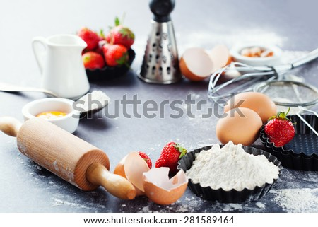 Ingredients and tools for baking - flour, eggs, rolling pin and fresh berries on the black background, selective focus - stock photo