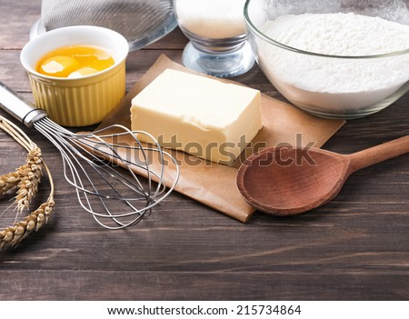 Ingredients and tools for baking on the wooden table close-up - stock photo