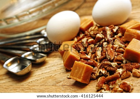 Ingredients and utensils to be used in baking a sweet and nutty dessert are spread out on a wood surface and ready to go.  Shallow depth of field. - stock photo