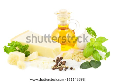 Ingredients for a green Italian pesto with parmesan cheese, herbs, olive oil, garlic, spices and pine nuts - stock photo