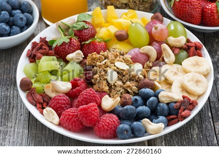 ingredients for a healthy breakfast - berries, fruit and muesli on wooden table, close-up, horizontal - stock photo