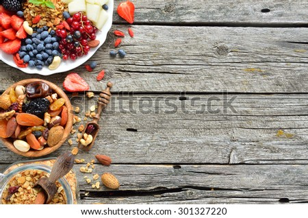 Ingredients for a healthy breakfast - berries, fruit, dried fruits and granola on the wooden background,  top view - stock photo
