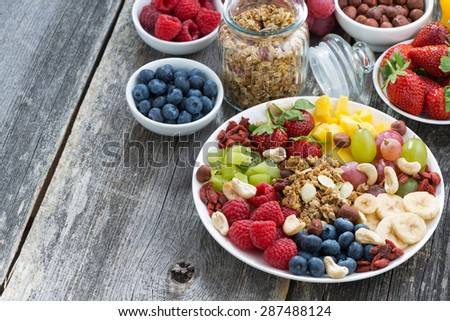 ingredients for a healthy breakfast - berries, fruit, muesli and wooden background, horizontal, top view - stock photo