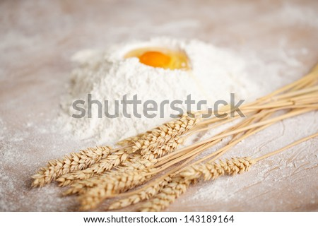 Ingredients for a loaf of fresh baked bread in a bakery with a bunch of ripe golden wheat lying alongside a pile of flour with a fresh egg broken into the top - stock photo