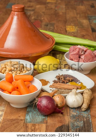 Ingredients for a Moroccan tagine dish with chick peas, lamb, carrots, celery, lemon, onion, cinnamon, star anise - stock photo
