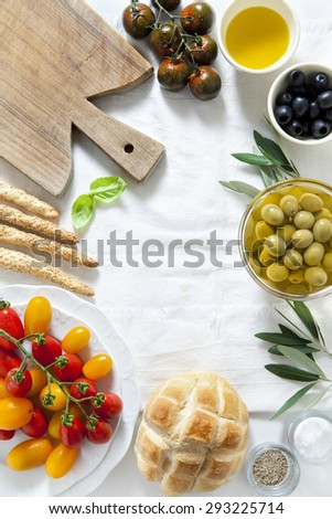 ingredients for a summer snack. summer products. sandwich with salami, red and yellow cherry tomatoes, green and black olives, black Sicilian tomatoes, bread sticks and olive oil. - stock photo
