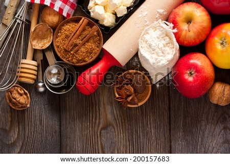 Ingredients for apple pie cooking. Fresh red apple, butter, flour, brown sugar, nuts and spices on a rustic wooden background.