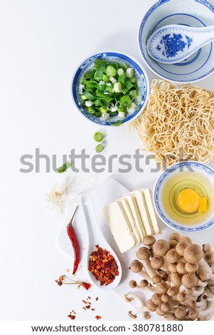 Ingredients for asian ramen soup. Noodles, spring onion, feta cheese, mushrooms, egg and chili pepper in asian porcelan bowls over white kitchen table. Top view