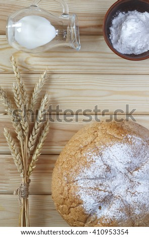 Ingredients for baking. A loaf of white wheat bread and wheat ears on the wooden table, top view, close-up.