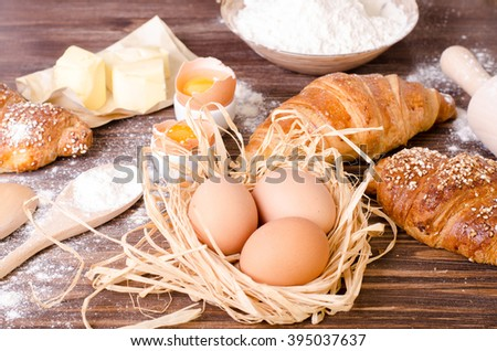 Ingredients for baking croissants - paper, flour, wooden spoon, rolling pin, eggs, egg yolks, butter served on a rustic wooden tray table.