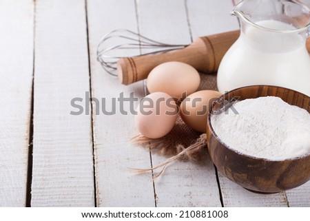 Ingredients for baking - eggs, flour, milk on white wooden background. Selective focus, horizontal. - stock photo