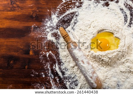 Ingredients for baking - flour, egg and rolling pin on dark wooden table with space for text - stock photo