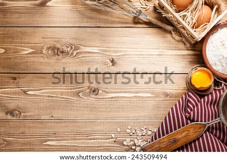 Ingredients for baking including eggs and flour, with sieve and whisk flour on empty wooden background with place for your text or recipes. - stock photo
