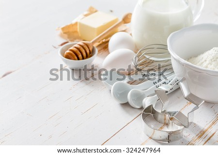 Ingredients for baking - milk butter eggs flour wheat, white wood background, copy space