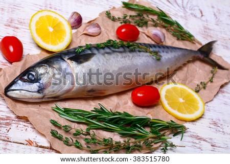 ingredients for baking scomber fillets, include raw mackerel, lemon, garlic, rosemary - stock photo