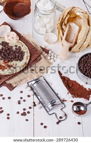 Ingredients for baking with chocolate. Choc chips, cocoa powder, sugar cubes and flour over white wooden background  - stock photo