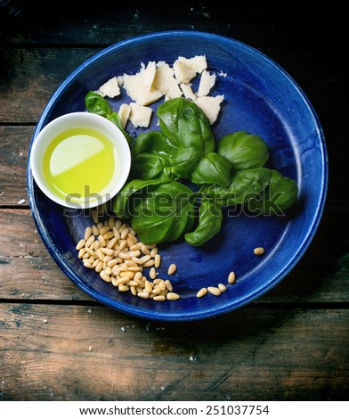 Ingredients for basil pesto served on blue ceramic plate over old wooden table. Top view - stock photo